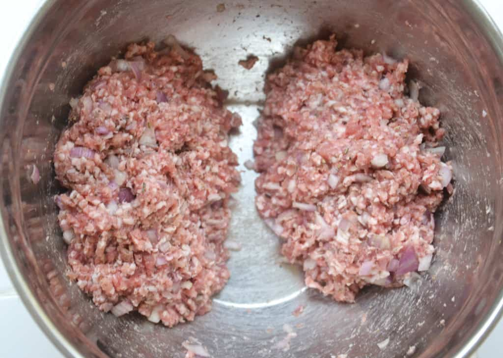 sausage meat formed into two portions in a bowl.