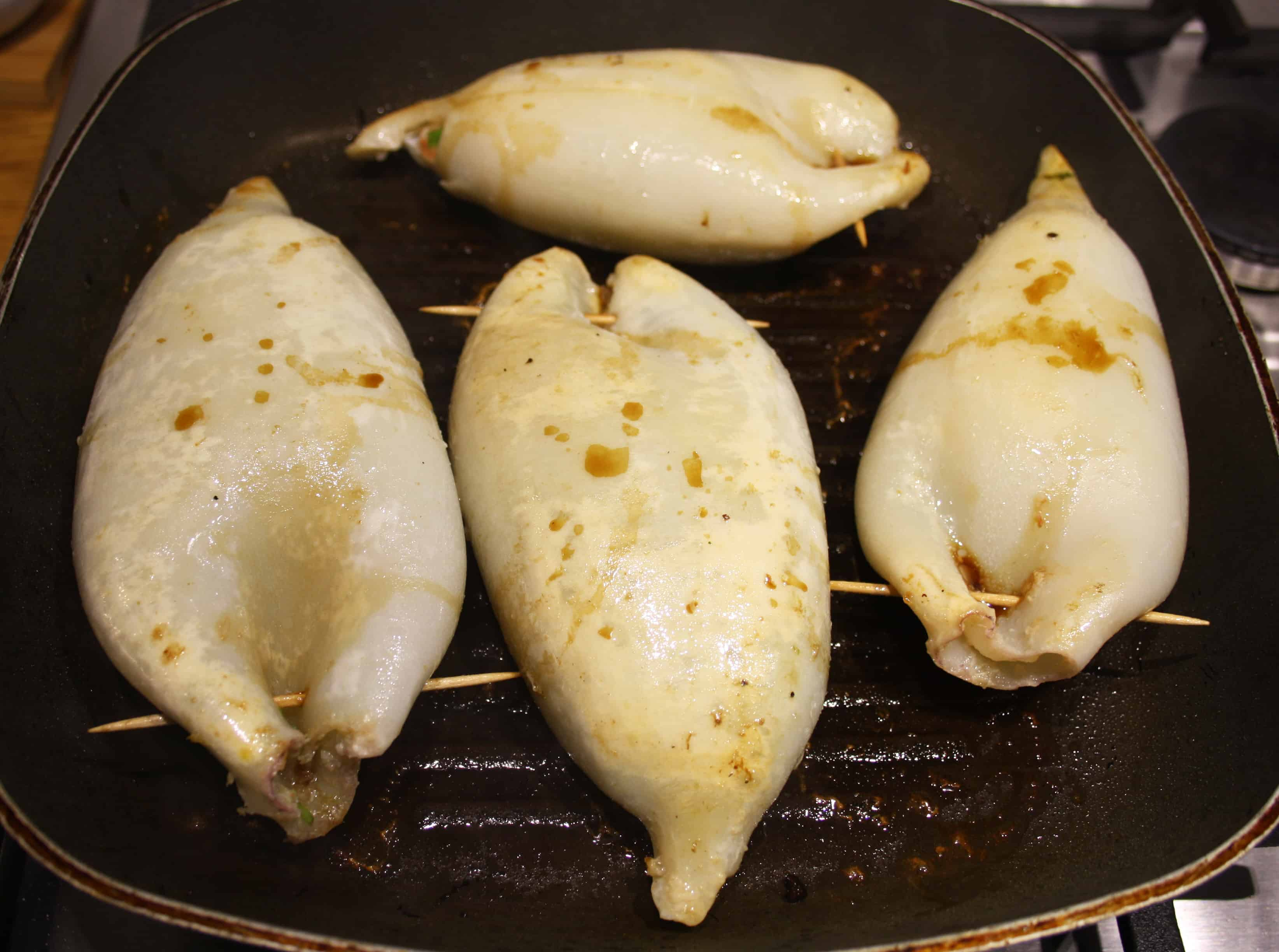 stuffed squid frying in a griddle pan.