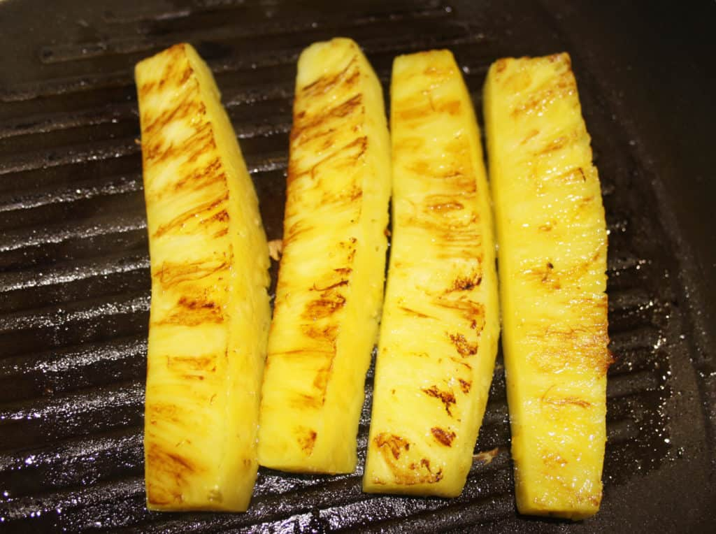 pineapple spears grilling in a griddle pan.