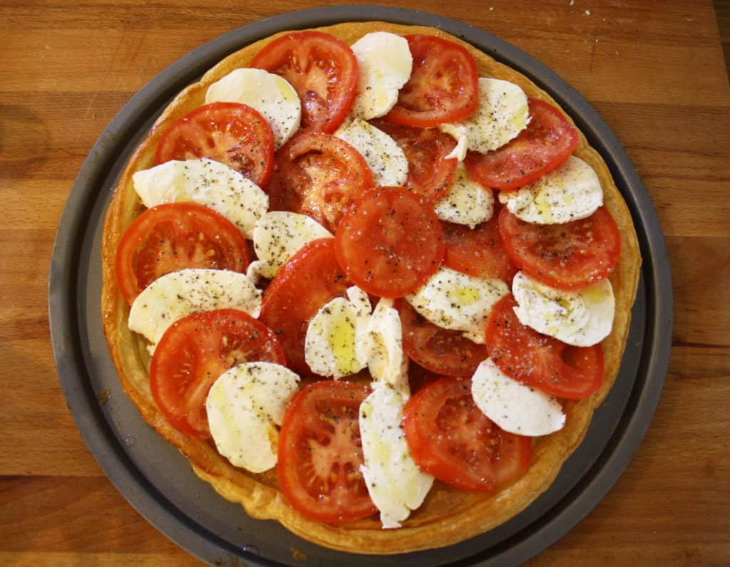 Make this simple Caprese tart in 30 minutes with tomatoes, mozzarella, fresh basil and shop bought puff pastry for a delicious vegetarian dish.