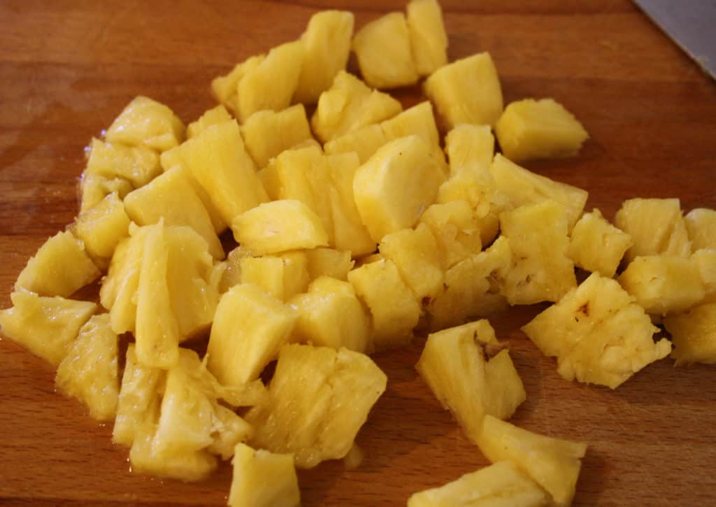 chopped fresh pinapple on a chopping board.