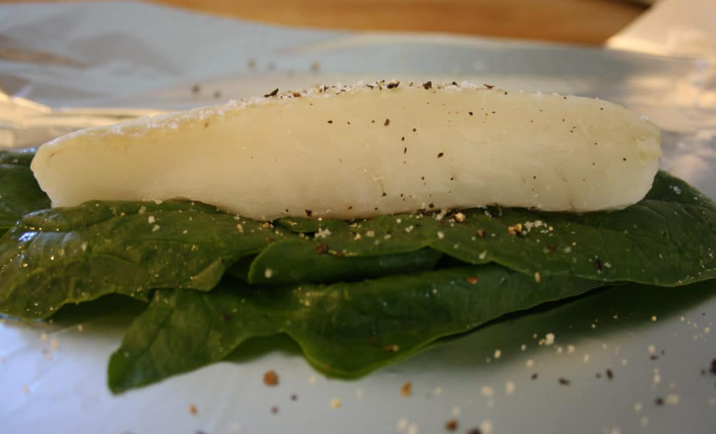piece of raw cod on a bed of spinach simply  on a piece of foil.