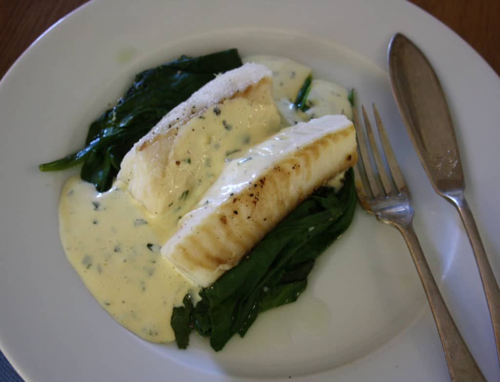 finished dish ofCod on a bed of spinach with a  sauce which is flavoured with basil.