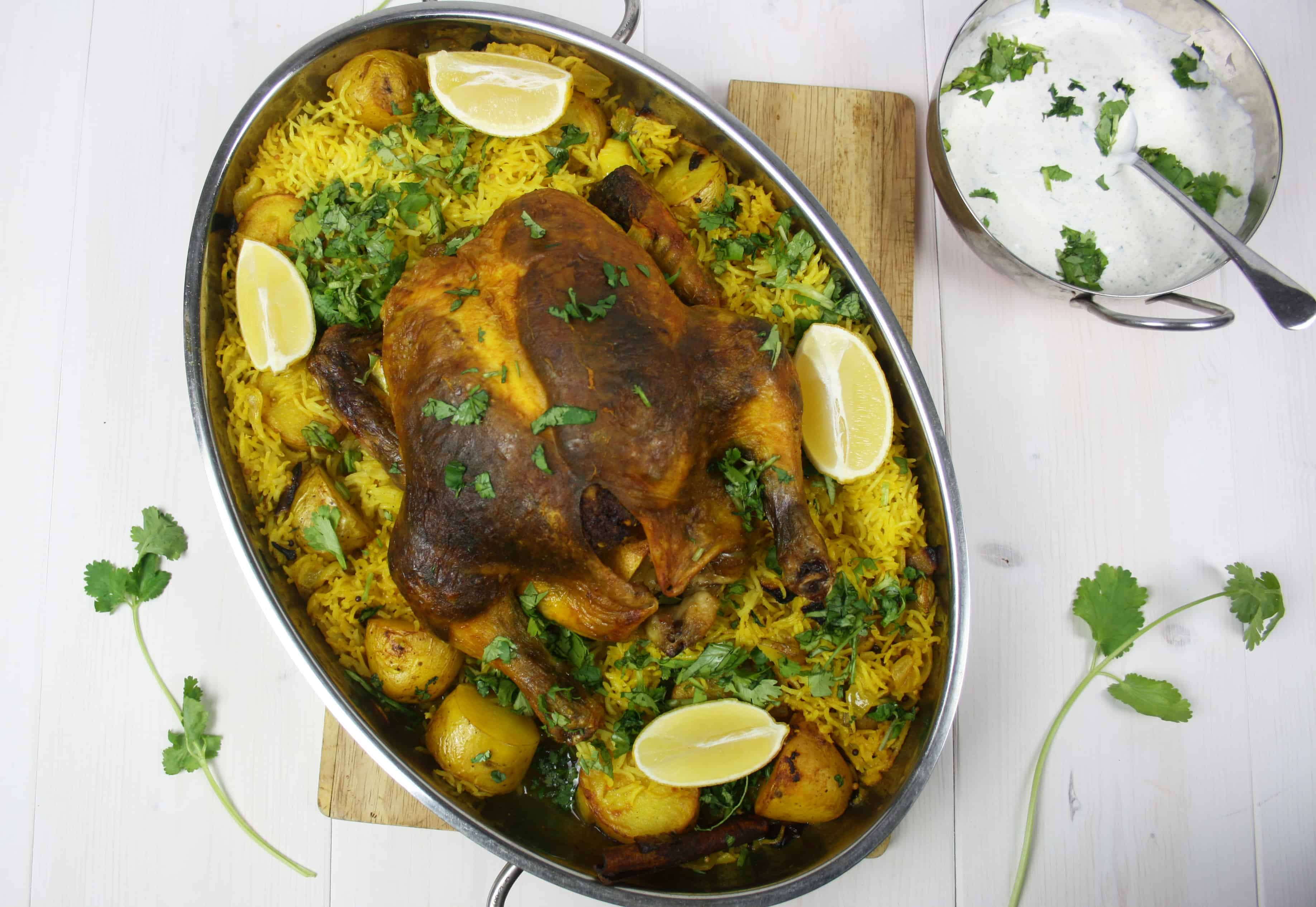 Asian Roast Chicken. This is a one pot dinner where a chicken is stuffed with spices and cooked with potatoes and rice and a bucketful of turmeric.