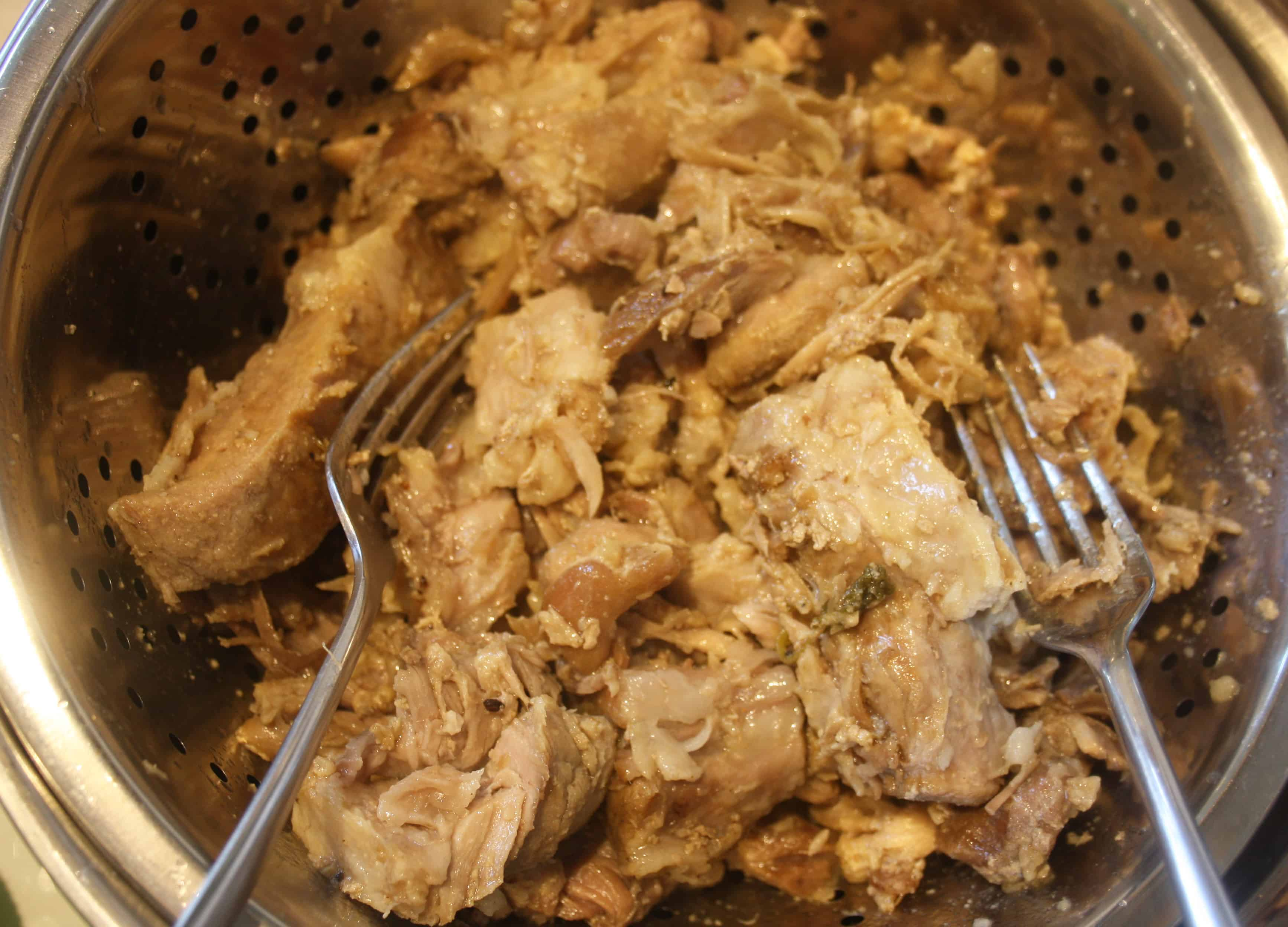 cooked pork draining in a colander.