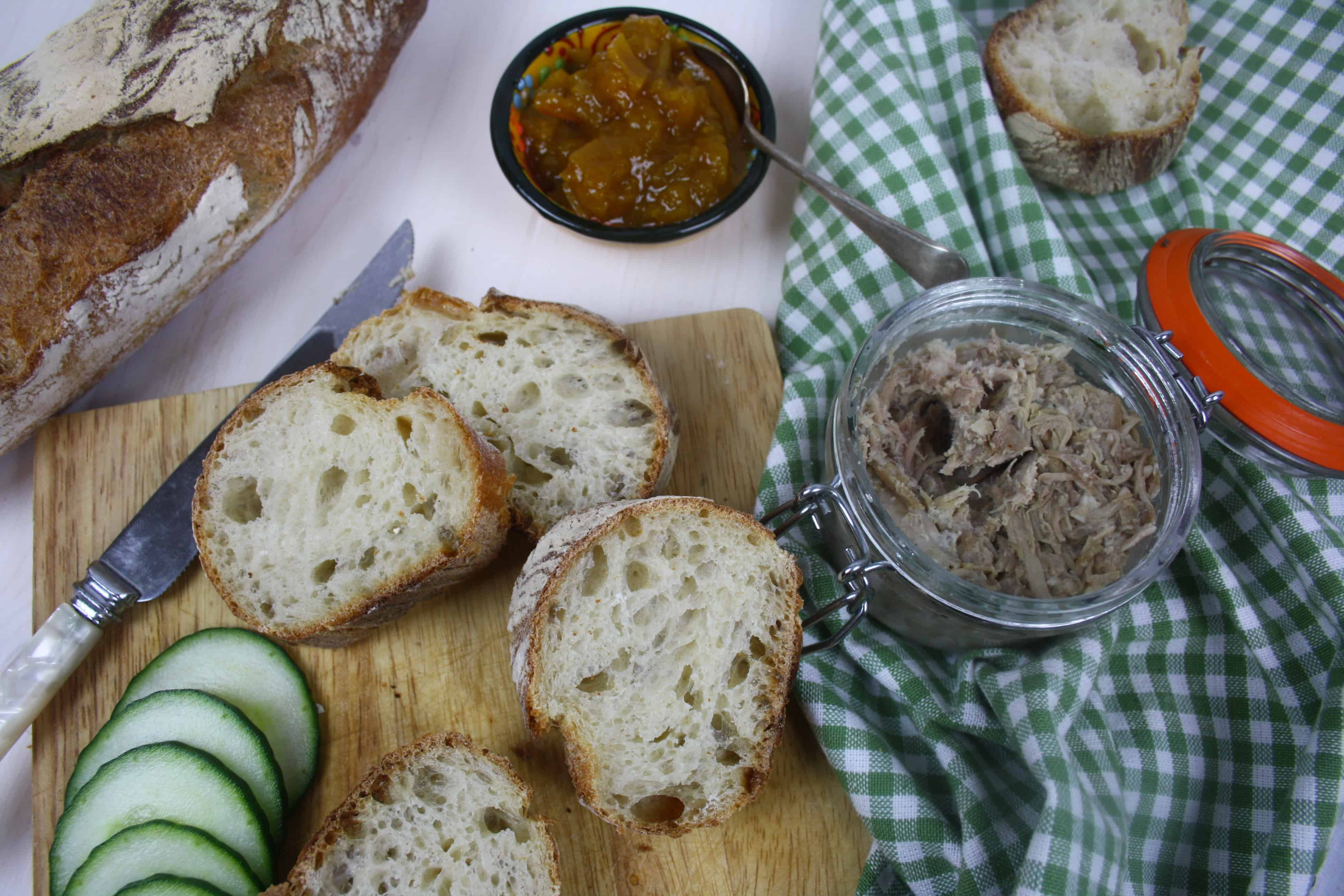 pot of cooked pork with bread slices and chutney.