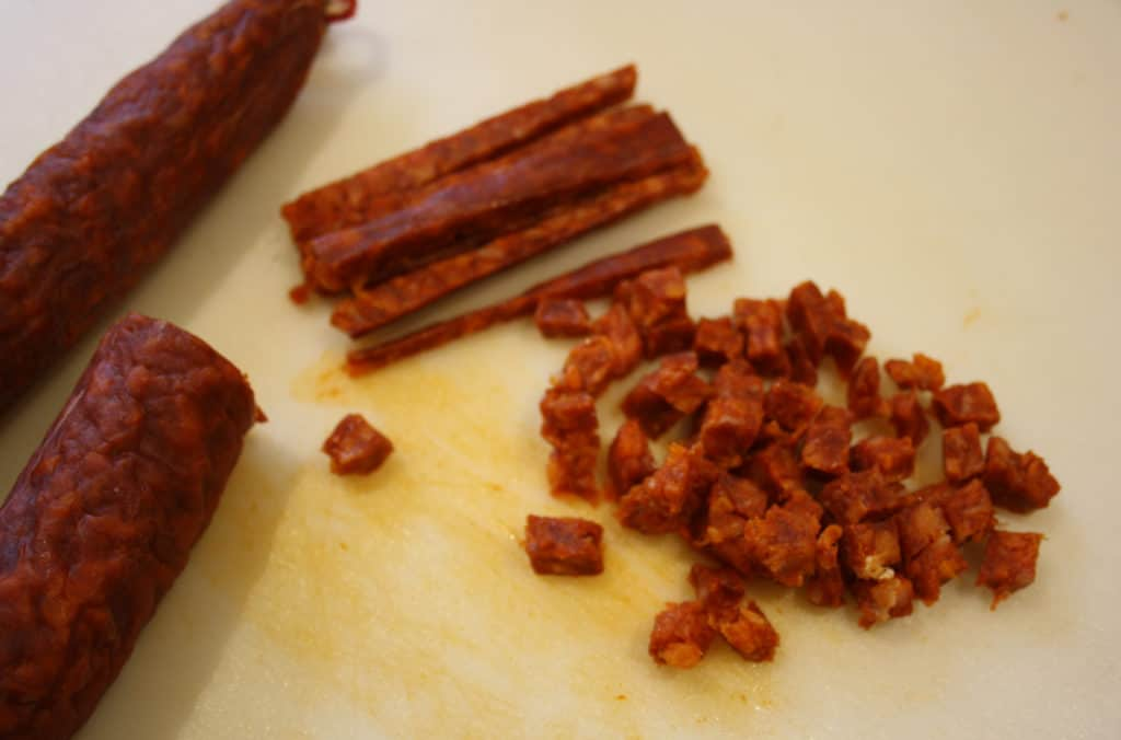 Piece of chorizo with some chopped in strips and some chopped finely