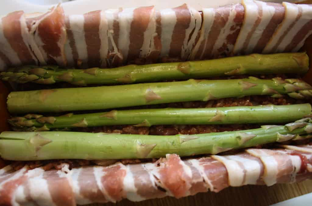 dish showing 4 asparagus spears laying lengthways.