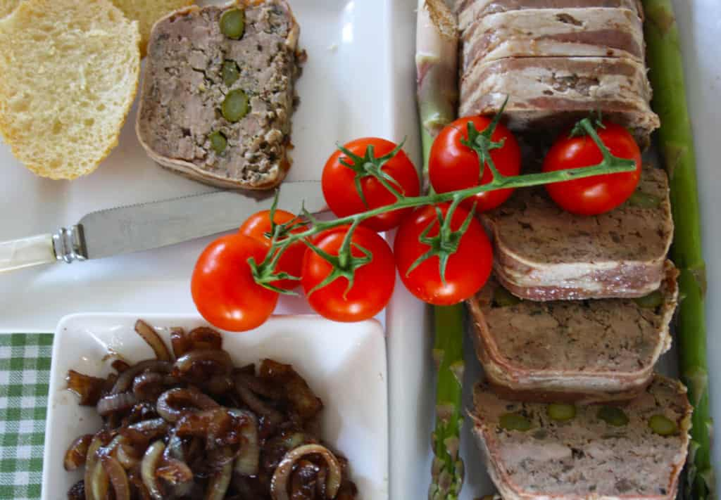 slices of terrine with bread, chutney and tomatoes.