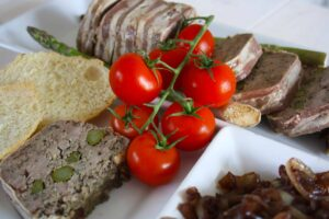 Duck Terrine with Asparagus. Layers of pork mince,liver, duck fillets and asparagus are all wrapped up in streaky bacon for a delicious starter.