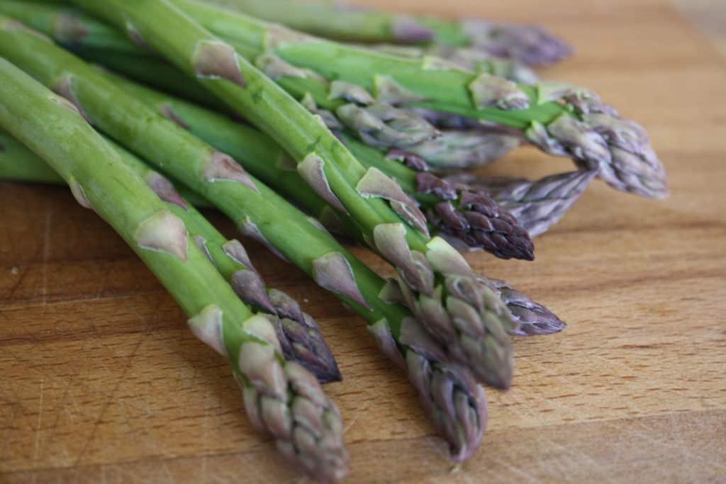 fresh asparagus spears on a chopping board.
