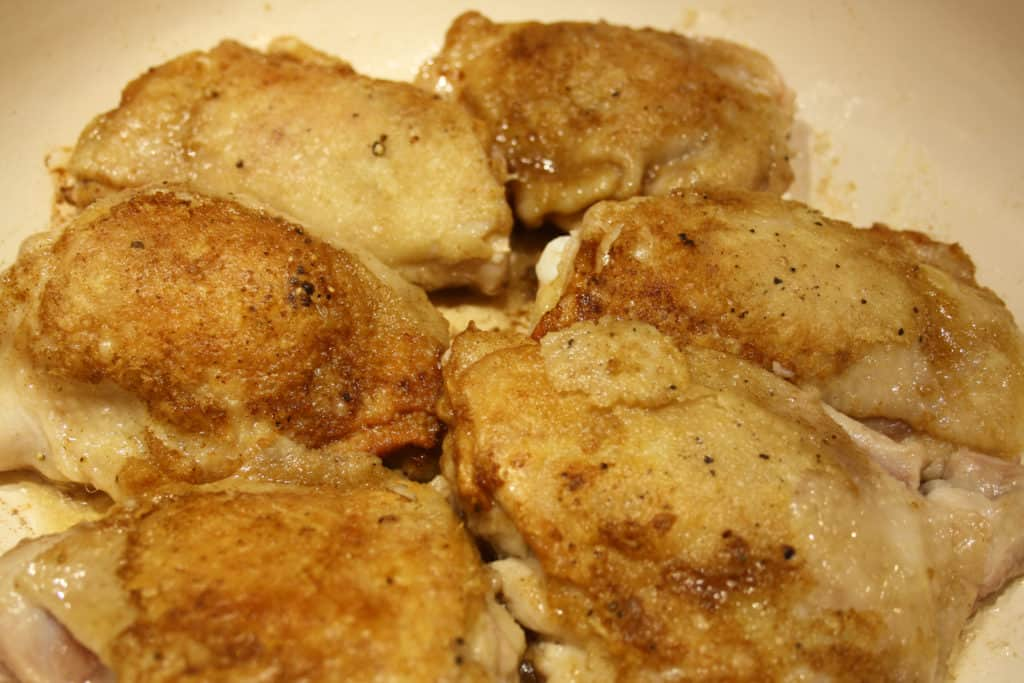 Chicken Thighs with browned skin uppermost in a frying pan