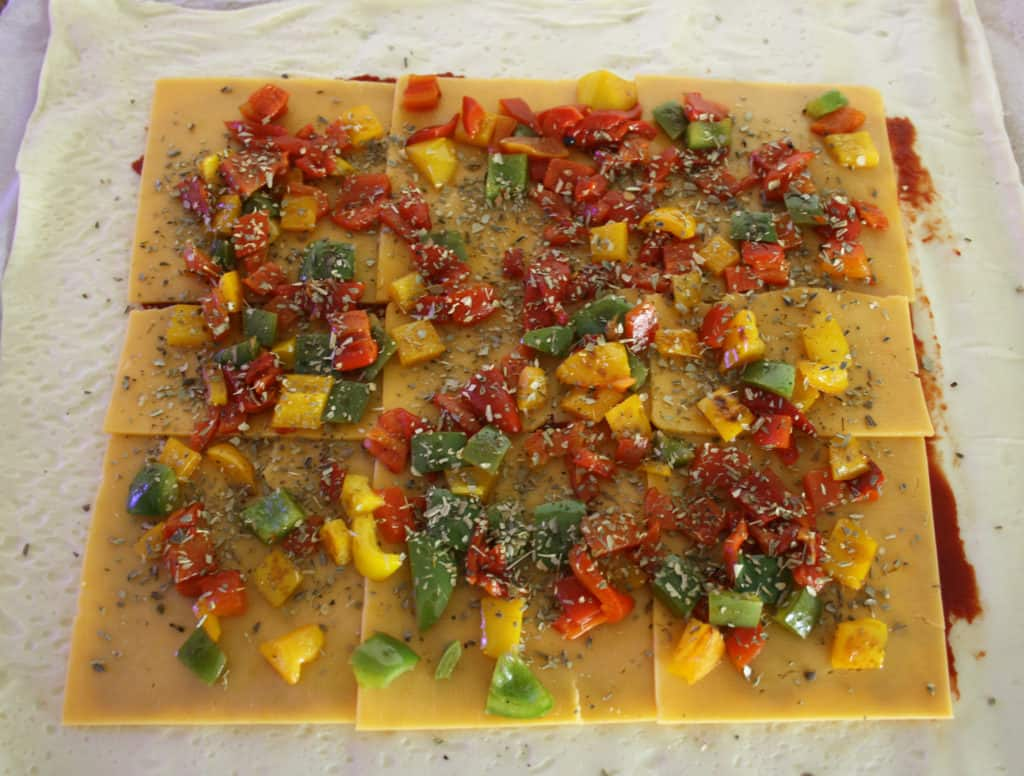pizza dough now topped with chopped mixed peppers.
