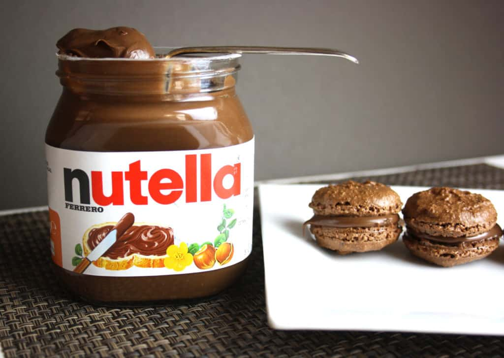 jar of nutella and two macarons on a plate