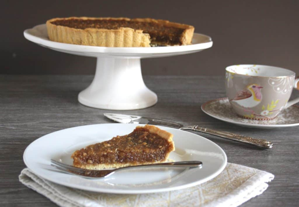 Treacle Tart gets a festive makeover with the addition of ginger, lemon zest and chopped pecans. Delicious served warm with cream!