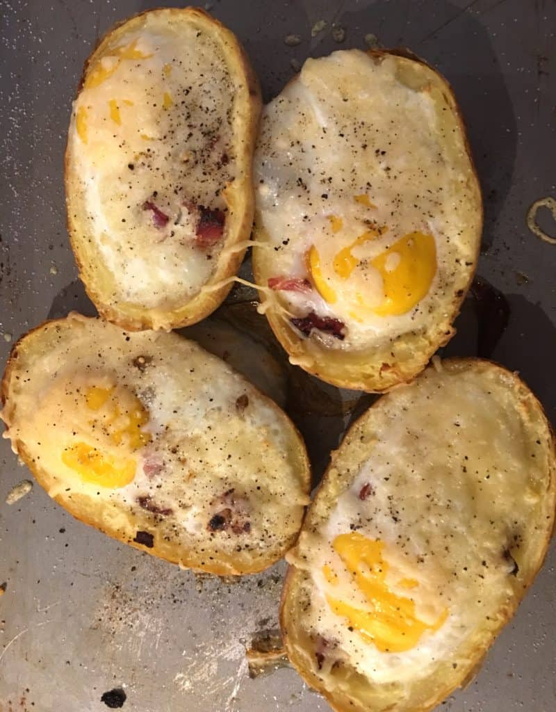 Baked Eggs in Potatoes with Bacon. Baked potatoes lined with bacon and egg and baked with cheese for a delicious breakfast or brunch treat.