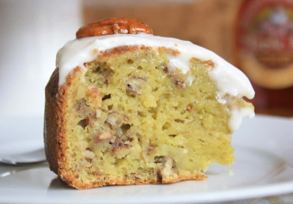 Slice ofPecan Banana Avocado Cake covered with icing.