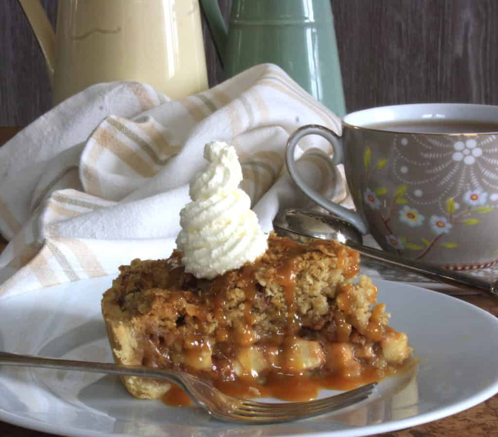 Apple  Crumble Tart slice with caramel pouring over the side