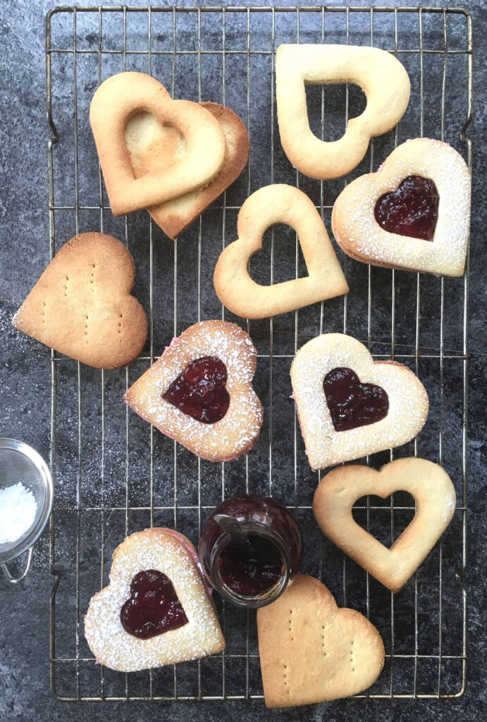 Heart shaped Linzer biscuits with jam filling on a cooling rack