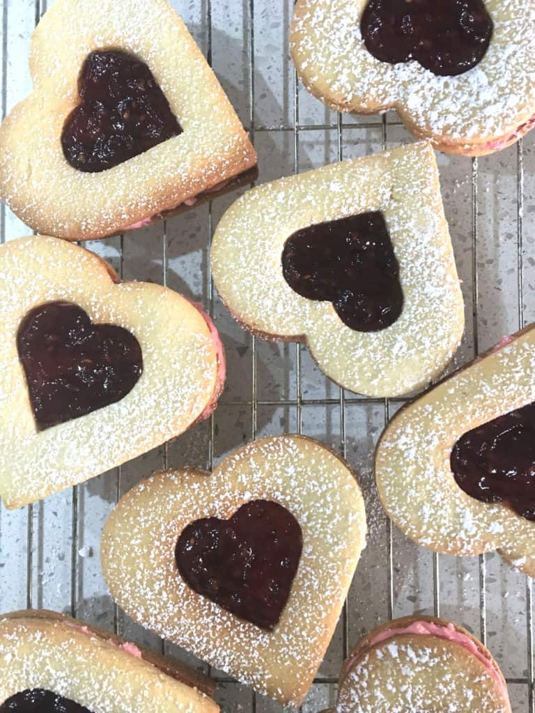 Aerial shot of finished heart shaped biscuits with jam centres.