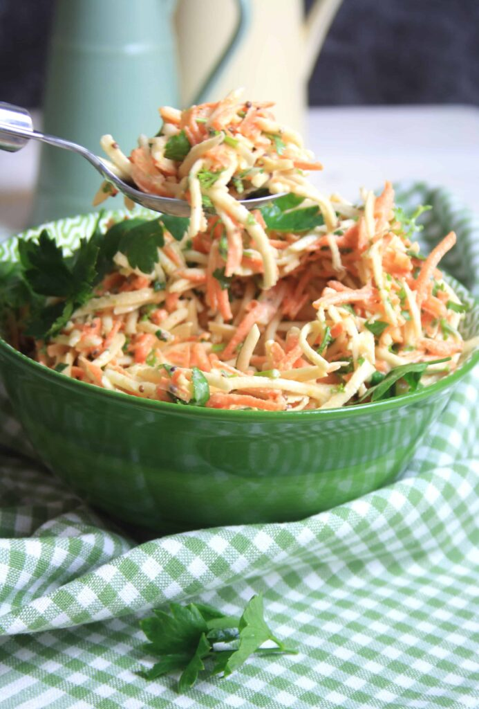 green bowl full of carrot and celeriac remoulade with a spoonful