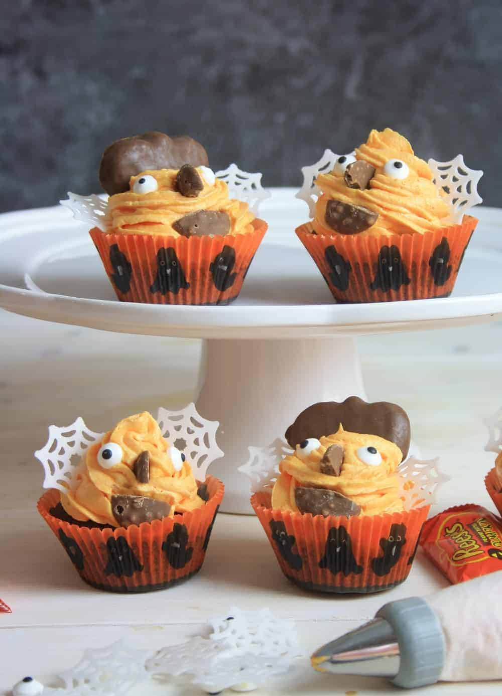 4 cupcakes decorated with Halloween decorations