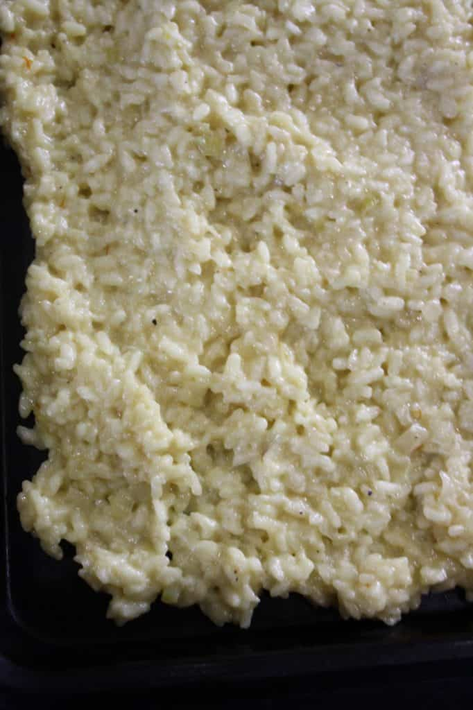 cooked risotto rice spread onto a tray