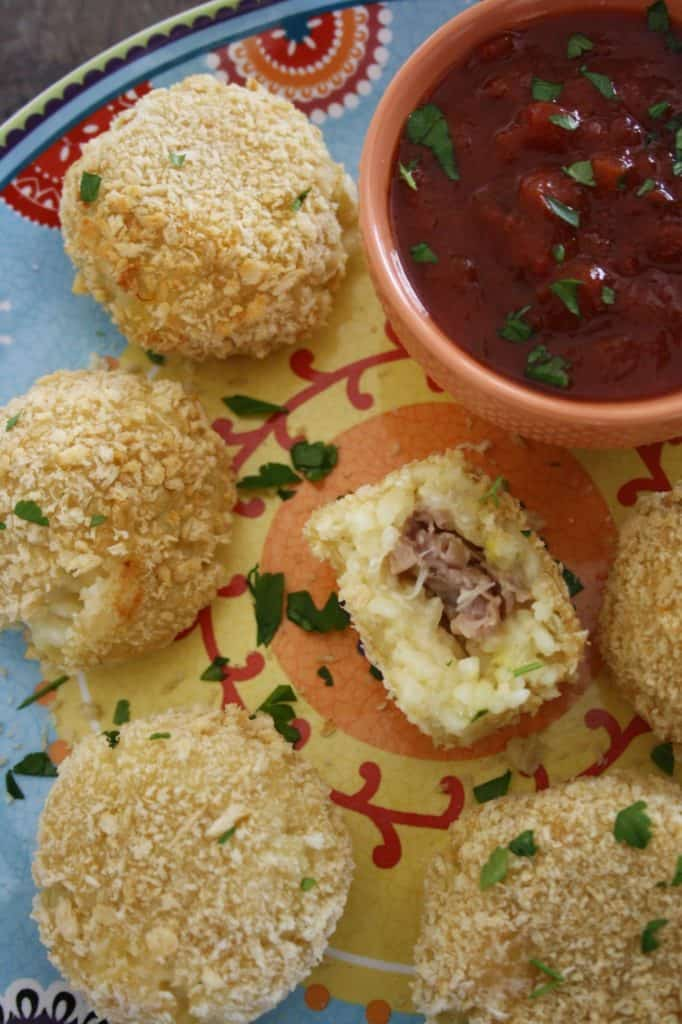 arancini on a plate with sauce