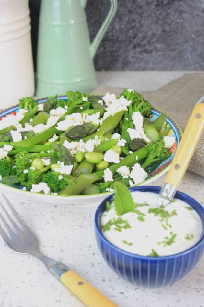 bowl of salad with broccoli and asparagus and endamame