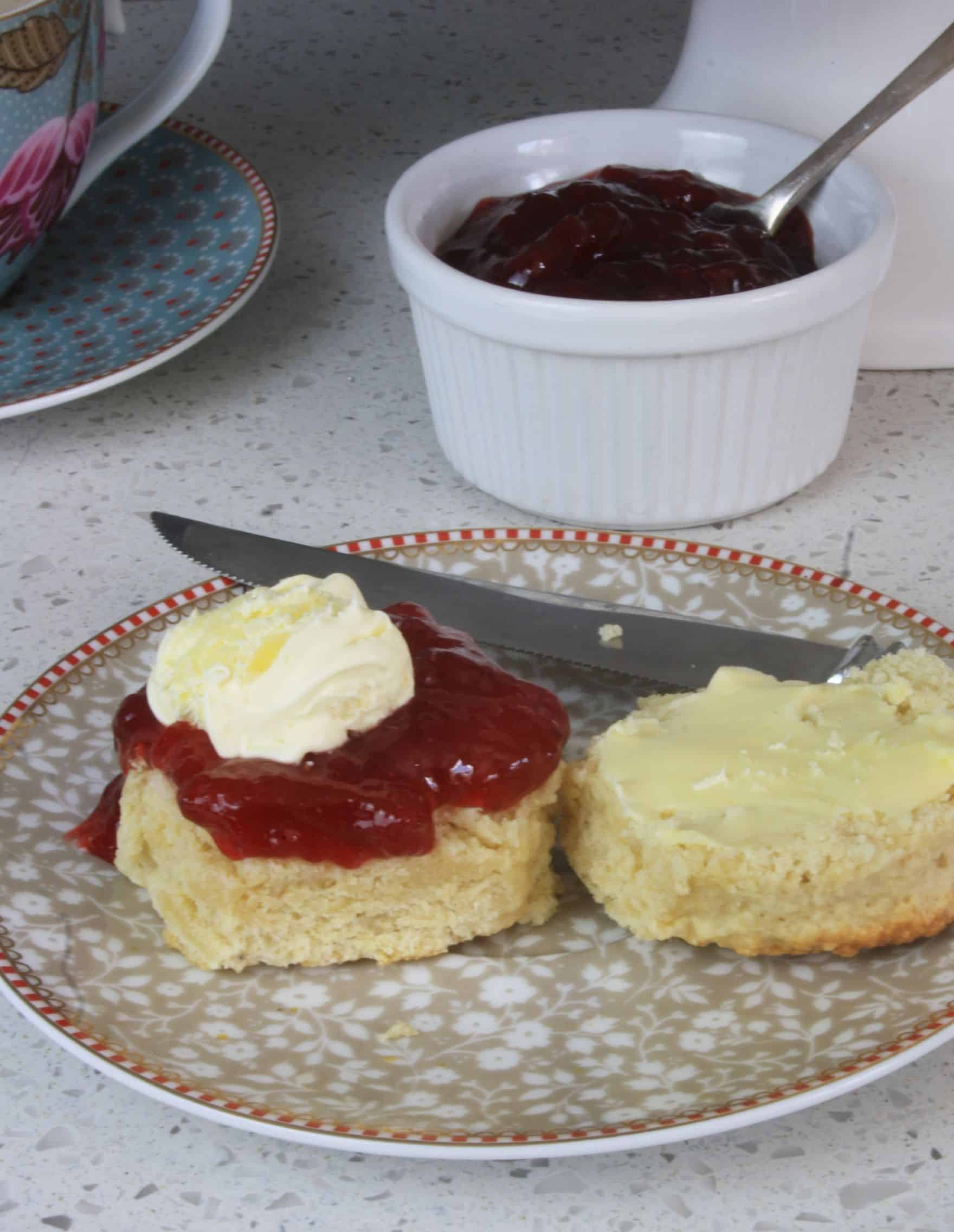 Plate with a cut scone topped with jam and cream