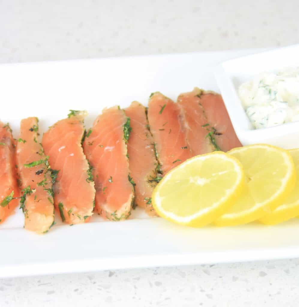 sliced fish in a plate with sliced lemons.