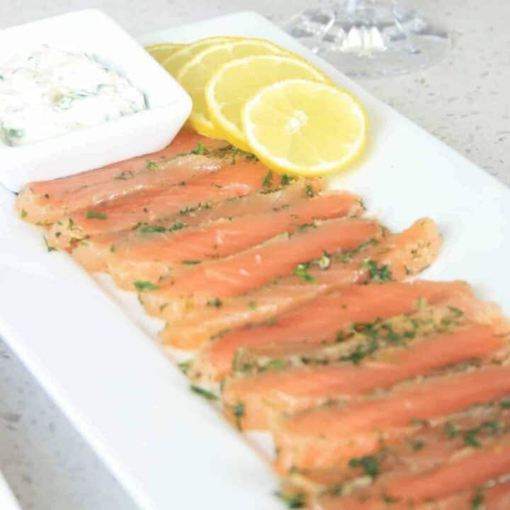 sliced cured salmon on a plate with lemon