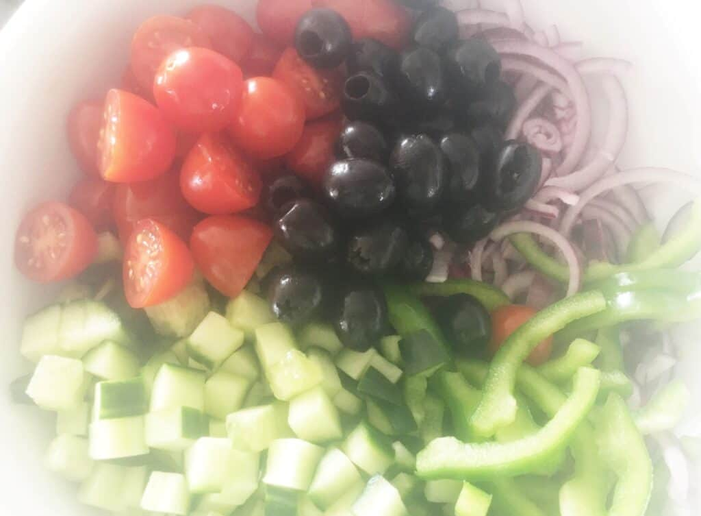 bowl with piles of olives, tomato, cucumber and red onion and peppers