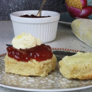 scone with jam and cream on top and pot of jam in background
