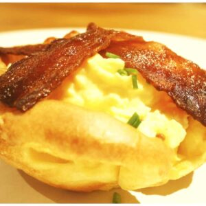 Yorkshire pudding filled with scrambled egg and topped with bacon