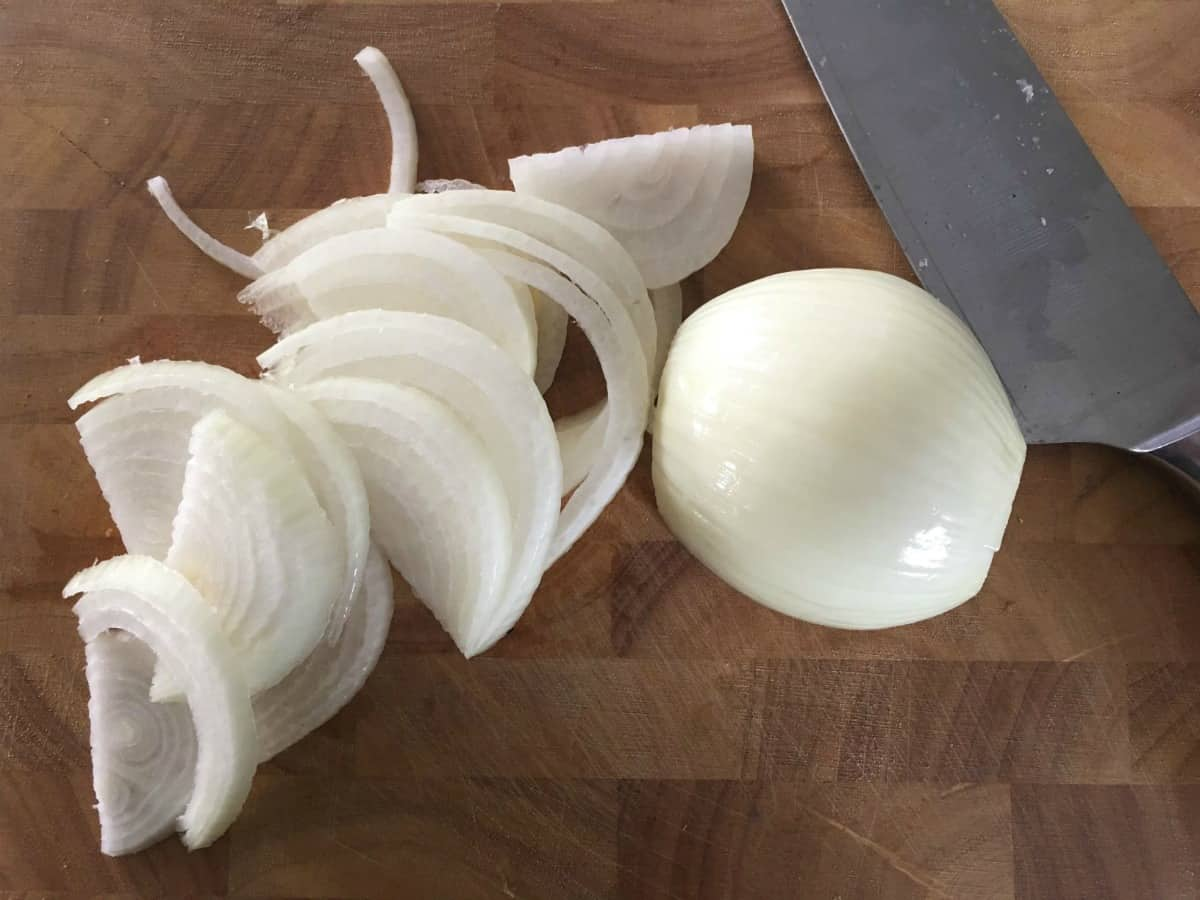 onions sliced on a chopping board.