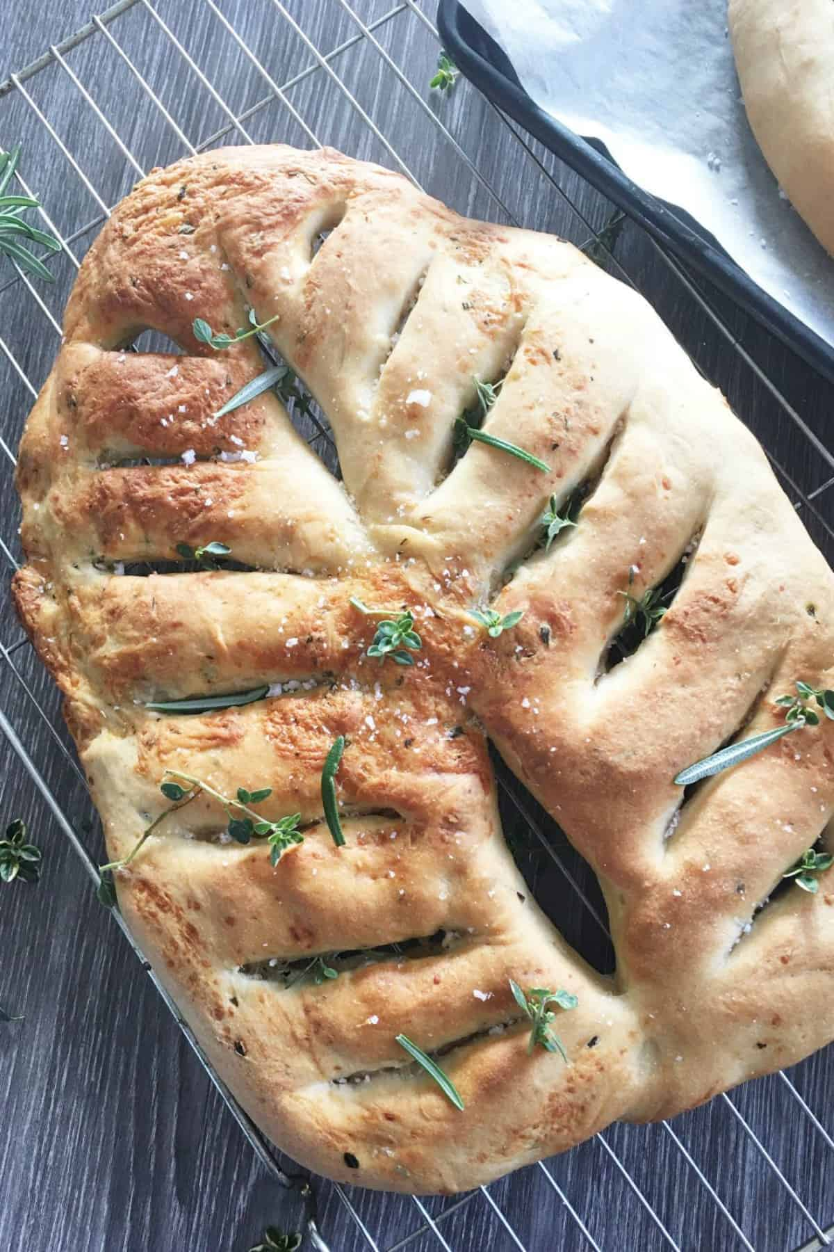 cooked bread on a rack with herbs sprinkled over