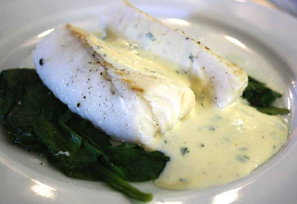 Cod fillets on aq plate wiht spinach and basil mousseline sauce poured over.