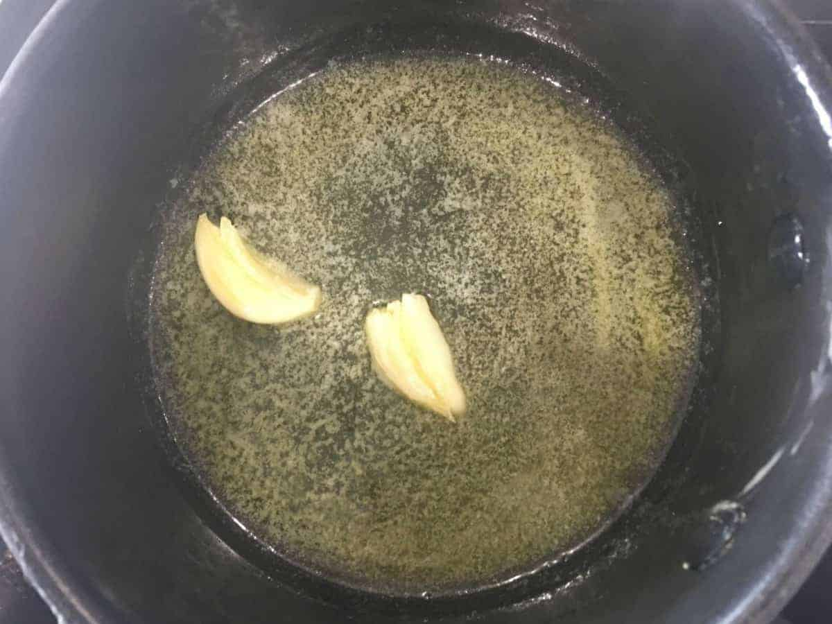 two cloves of smashed garlic in melted butter in a saucepan.