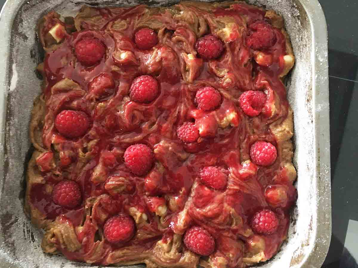 pan with raspberries pushed into the mixture and swirled with puree.