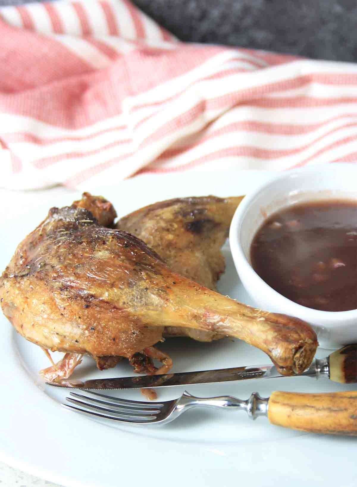 duck confit with pot of sauce and cutlery.