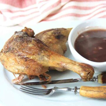 duck legs with redcurrant sauce in a bowl with a knife and fork.