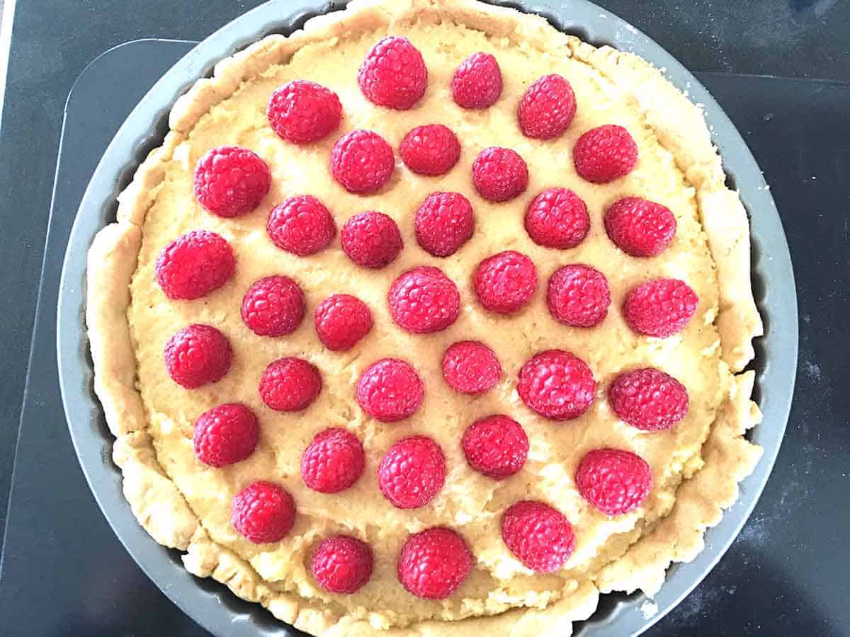tart with filling added and raspberries pushed in.