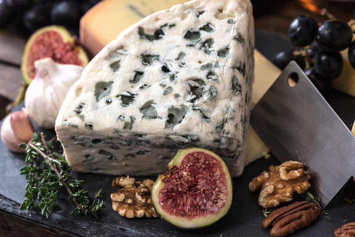 big wedge of blue cheese surrounded by nuts and fruit.