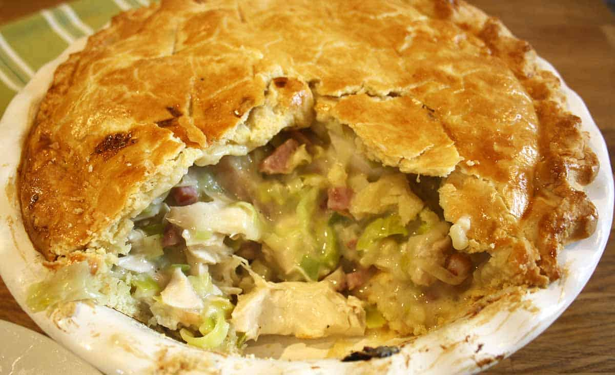 chicken and leek pie with bacon with a portion cut out.