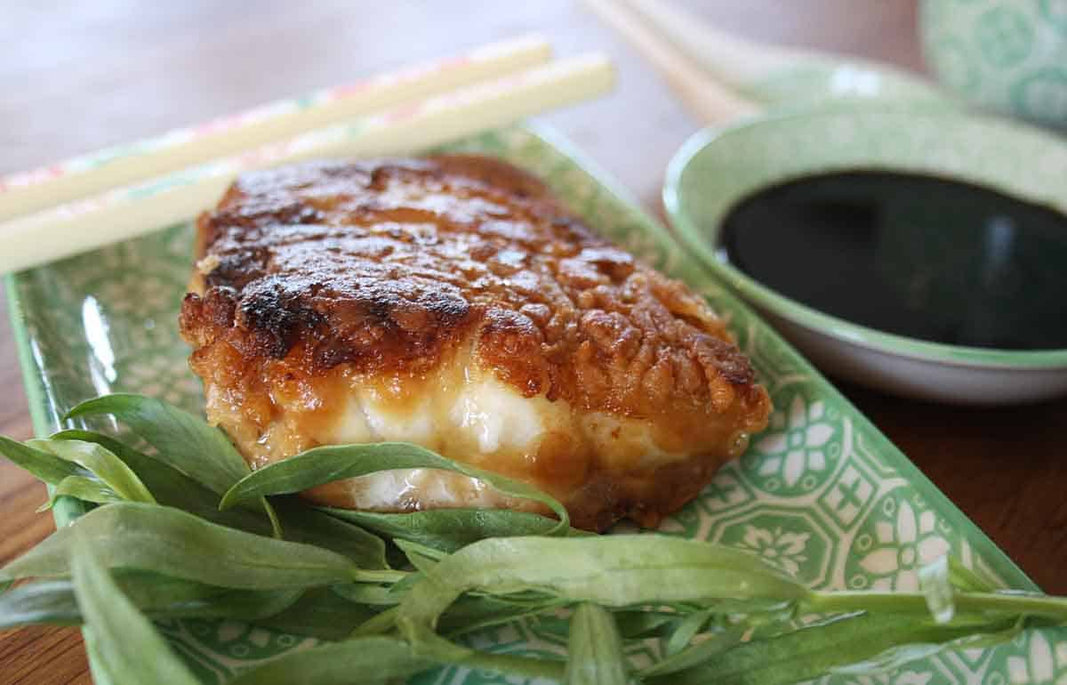 crispy miso cod on a plate with a dipping sauce in a pot.