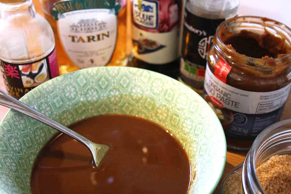 marinade ingredients of sherry, miso paste, sugar and mirin around a bowl with marinade inside.