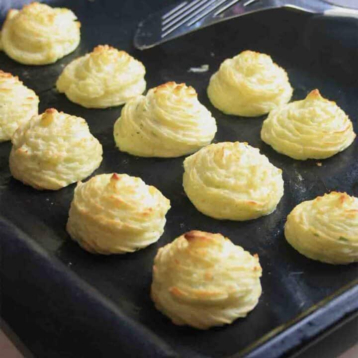 piped swirls of potato on a baking tray.
