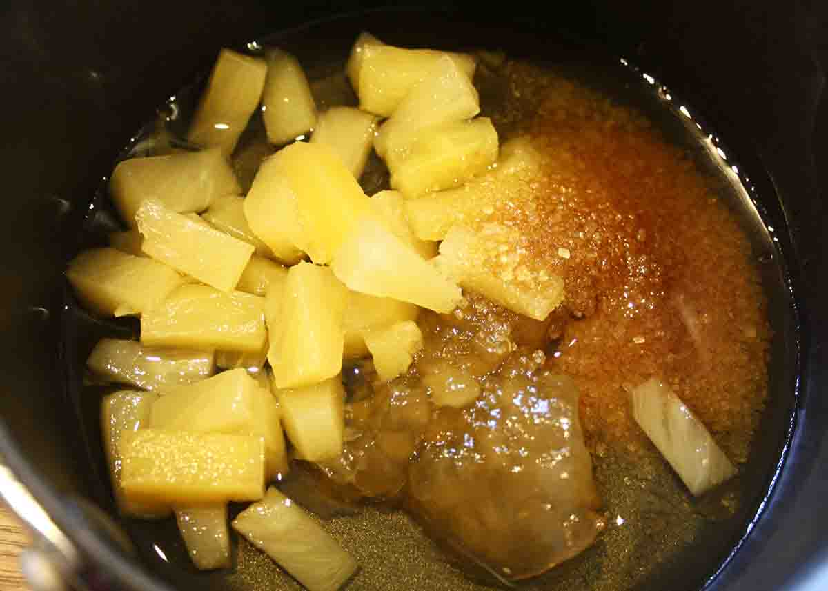saucepan with ingredients for sauce including pineapple, marmalade, sugar and Bourbon.