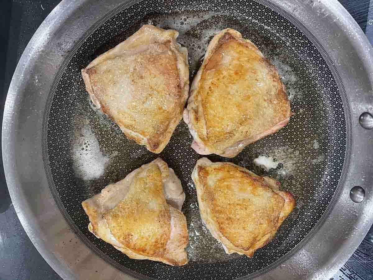 chicken thighs skin side up with golden skin in a frying pan.